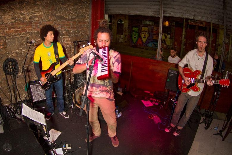 Depois do jogo Brasil x Camarões pela Copa do Mundo, a banda Muzamba deu início a noite tocando os clássicos do dub e do reggae. Na foto Angelo B no baixo, Bruno Pederneiras na guitarra e o vocalista André Machado na escaleta. Fotos: Radio Layback