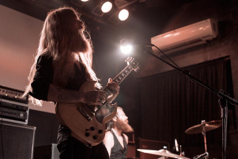 Lupus, uma vasta seleção de pedais e uma de suas Gibson SG, de uma coleção de várias delas dos anos 60 e 70. O timbre que ele tirava parecia vir direto dessa época também. Foto: Radio Layback